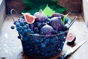 färska fikon, druvor, katrinplommon och daggbär foto