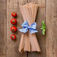 pasta, tomater och basilika på träbakgrund foto