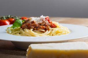 spaghetti med bolognese sås parmesan och basilika foto