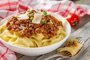 pasta bolognese i vit skål med sallad och tomater foto
