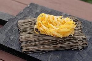 två typer av pasta på träplanka foto