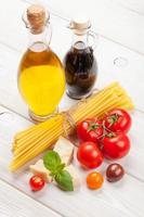 pasta, tomater, basilika på träbord foto
