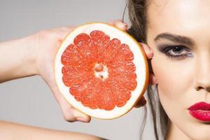 vacker flicka håller grapefrukt snitt i halva foto