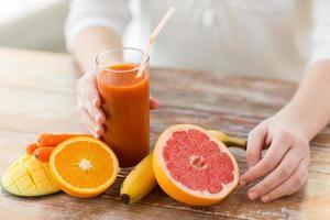 närbild av kvinnahänder med juice och frukter foto
