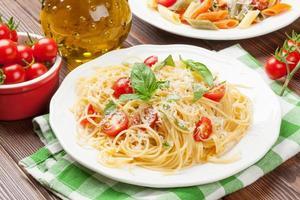 spaghetti och penne pasta med tomater och basilika foto