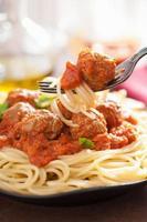 spaghetti med köttbullar i tomatsås på gaffel foto