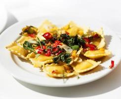 ravioli garnerad med basilikablad på den vita plattan foto