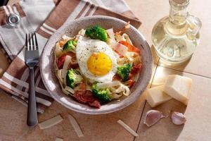 tagliatelle pasta med broccoli, prosciutto och stekt ägg.