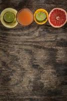 saftglas och färsk citrusfrukt på rustikt trä foto