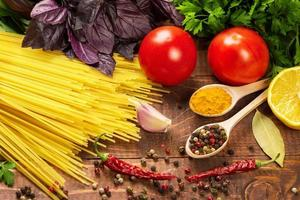 rå pasta, grönsaker, basilika och kryddor på träbordet foto