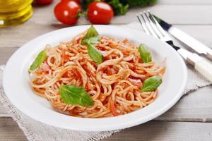 pasta med tomatsås på plattan på tabell närbild foto