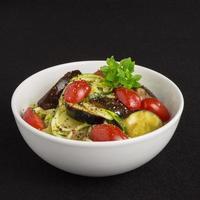 vegetariska zucchininudlar med aubergine och tomater foto