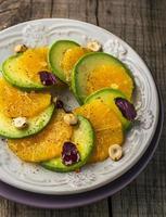 förrätt av avokado, apelsin med lila basilika och hasselnötter foto