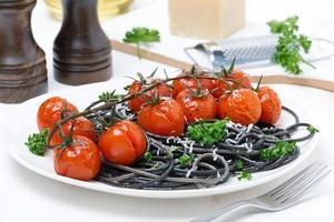 svart pasta med bakade tomater och persilja foto