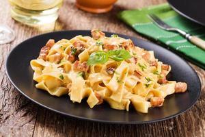 pasta carbonara med bacon, basilika och ost