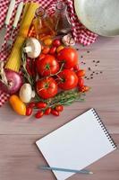 kryddor, pasta och grönsaker runt anteckningsboken. foto