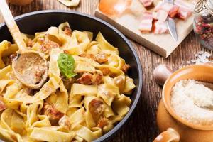 pasta carbonara med bacon, basilika och ost foto