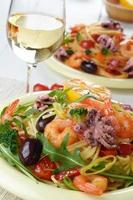 skaldjurspagettipastarätt med bläckfisk och räkor foto
