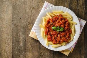 pasta med tomatsås på träbord foto