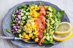 lax, avokado, majs, gurka och lök sallad foto