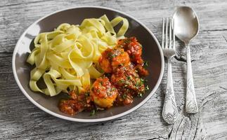 kycklingköttbullar i tomatsås och fettuccinpasta foto