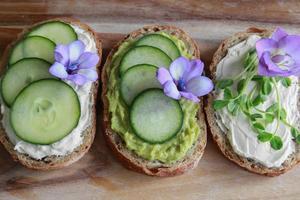 grön gräddbröd med öppet ansikte, smörgåsar med lila ätliga blommor foto