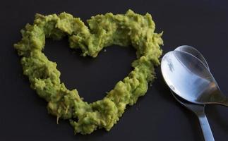 grön massa avokado i en hjärtaform.