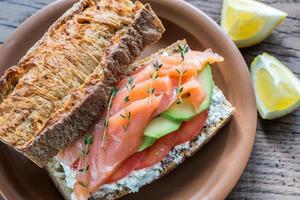 smörgås med lax, avokado och tomater foto