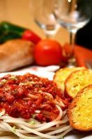 spaghetti serveras med bröd på en tallrik
