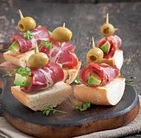 mellanmål på rostat bröd med skinka, avokado och oliver foto