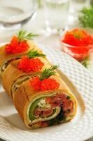 rulla pannkakor med röd fisk och avokado. foto