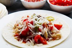 nötkött och kycklingfajitas med färgglada paprika i tortill foto