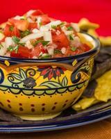 skål med kryddig salsa och majschips foto