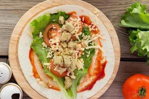 tortilla med kyckling, tomater, sallad foto