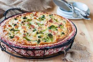 quiche med skinka och broccoli på ett träbord foto