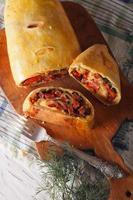paj med skinka, ost och örter närbild. vertikal toppvy foto