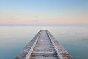 tom brygga som leder mot havet vid solnedgången