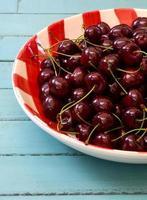 färska körsbär i röd ginghamplatta foto