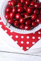 söta körsbär på plattan på träbakgrund
