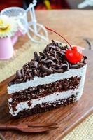 svart skog, chokladkaka på träbord foto