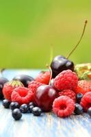 olika mjuka frukter jordgubbar hallon körsbär blåbär på bordet foto