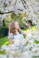 vacker flicka i trädgården för körsbärsröd blomning foto