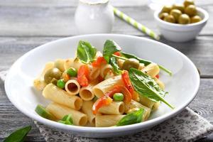 läcker pasta med spenat och gröna ärtor foto
