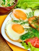 engelsk frukost, äggröra med rostat bröd, bacon, skinka, grönsaker foto