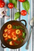 hemlagad tortellinisoppa med tomat, basilika och spenat foto