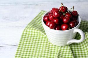 söta körsbär i mugg på träbakgrund foto