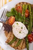 pocherat ägg på rostat bröd med sparris, tomater och greener foto