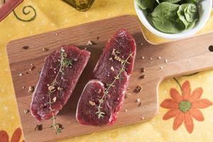 rått nötkött av svin med kryddor över ett träbord foto