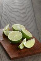 skivade limefrukter på träplatta foto
