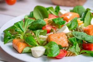 närbild av lax med grönsaker och sallad foto